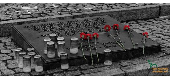Grabeskerzen und rote Rosen auf Gedenkstein mit hebräischer Aufschrift für die Opfer des Konzentrations- und Vernichtungslagers Auschwitz. Rechts unten zusätzlich eingefügt: Auf dass Auschwitz nie wieder sei!