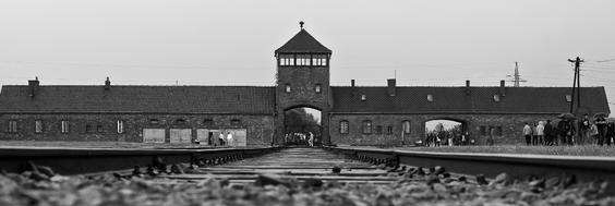 Schwarz-Weiß-Aufnahme von den Eisenbahnschienen und dem Eingangstor ins Konzentrations- und Vernichtungslager Auschwitz