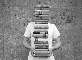 Person trägt einen Stapel Bücher, der seinen Kopf überragt.